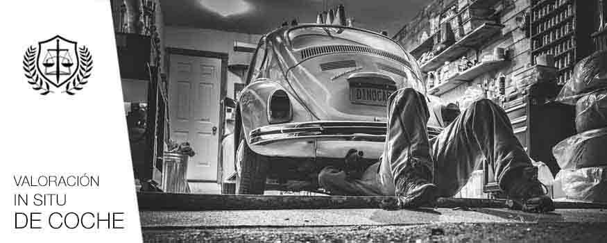 Hombre analizando coche de segunda mano siniestrado en taller